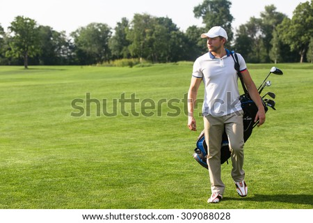 Golf and golfer concepts. Golf player in  trucker hat walking and carrying bag with golf clubs on course during summer time.  - stock photo