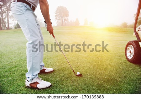 Golf approach shot with iron from fairway at sunrise