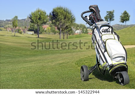 Golf bag in a golf course with a green background and blue sky - stock photo