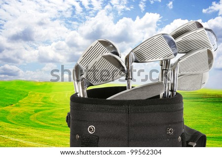 Golf bag with clubs against a beautiful fairway and a blue sky - stock photo