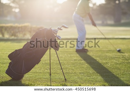 Golf bag with man in background during sunny day - stock photo