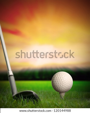 golf ball about to be hit with club from tee at sunset - stock photo