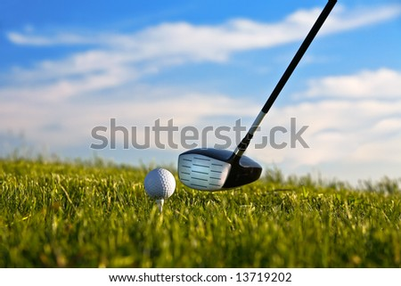 Golf ball about to be struck by driver with grass and blue sky.