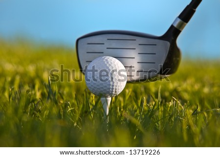 Golf ball about to be struck by driver with grass and blue sky - close up.