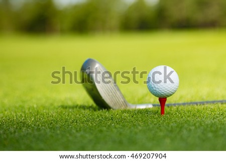 Golf ball and club on course with beautiful landscape