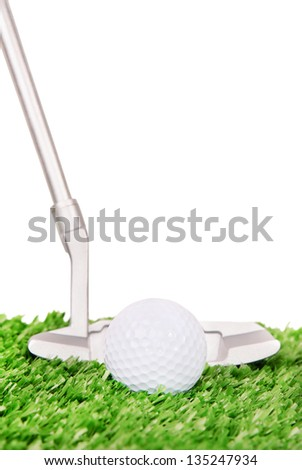 Golf ball and club on green field grass
