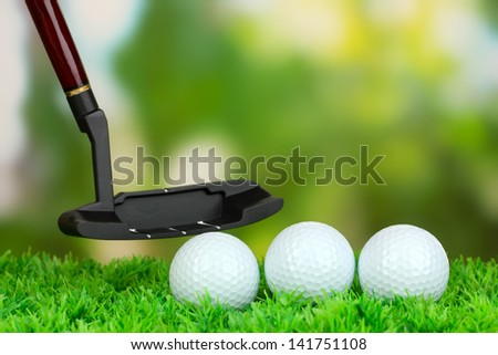 Golf ball and driver on green grass outdoor close up - stock photo
