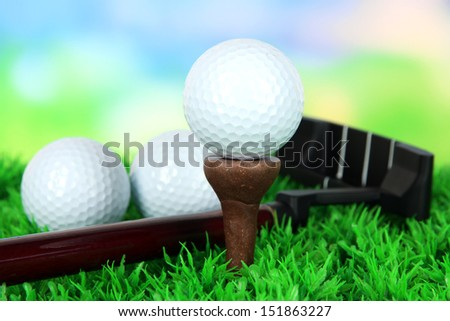 Golf ball and driver on green grass outdoor close up