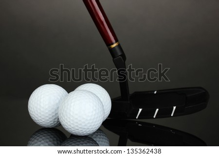 Golf ball and driver on grey background