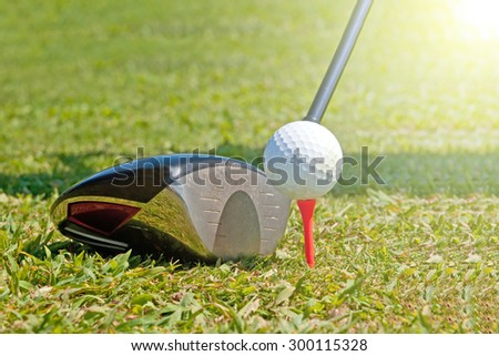 Golf ball and driver, ready to strike, on a real golf course. - stock photo