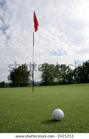 golf ball and flag -- short putt. Focus on ball
