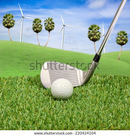 Golf ball and golf club with wind turbine on hill background  - stock photo
