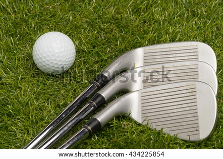 Golf ball and golf clubs with steel shaft on grass. - stock photo