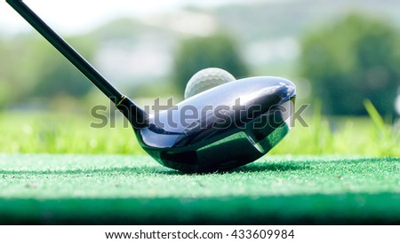 golf ball and putter on green grass of course - stock photo