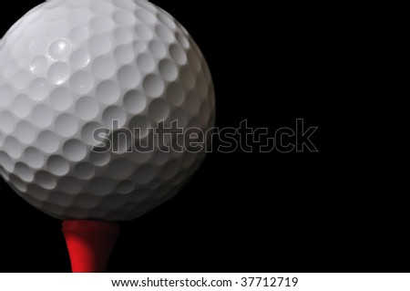 golf ball and tee isolated on black background