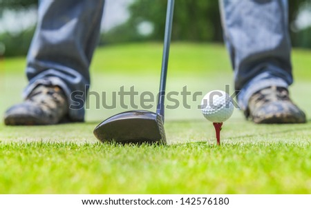 Golf ball behind driver at driving range, plenty of copy-space and very shallow depth of field. - stock photo