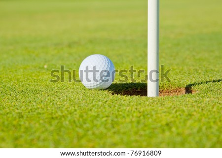 golf ball close to (going into) the hole(cup) with the flag still in close up selective focus