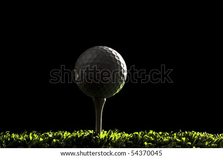Golf ball close up on tee at night , black background with copy space on right - stock photo