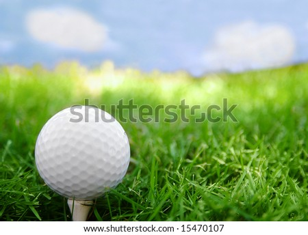 Golf ball closeup, on the tee, with grass and sky
