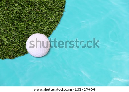 Golf ball edge of grass field and water.