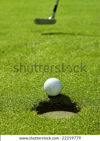 Golf ball falling into the hole
