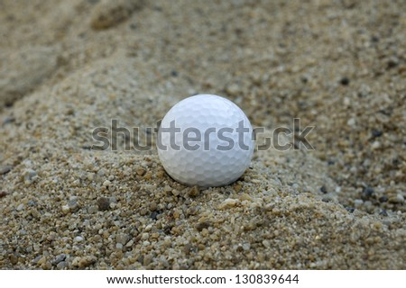 Golf ball in a sand trap. - stock photo