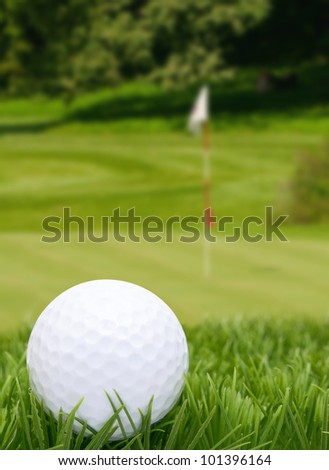 Golf Ball in Grass -  Green With Flag in Background - stock photo
