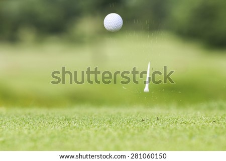 Golf ball just coming off the tee after hit by driver  - stock photo