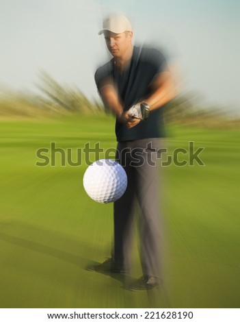 Golf ball just coming off the tee from a golfer in swing - stock photo