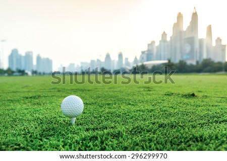 Golf ball lying on the grass in front of Dubai skyscrapers. Golf courses. Players are trained to play golf on the golf course. Close-up view of a golf ball - stock photo