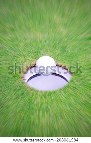 Golf ball move to the hole, motion blur, hole in one shot. - stock photo