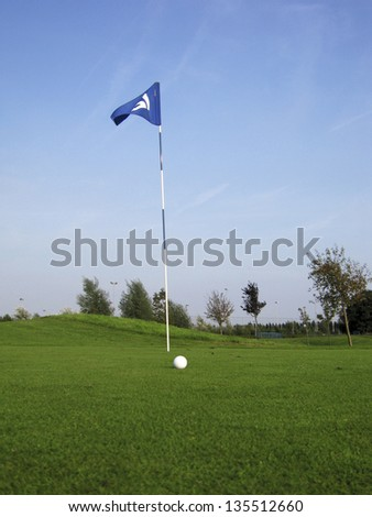golf ball near hole with flag and number - stock photo