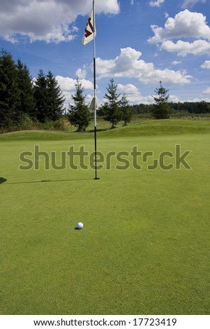 golf ball next a flag on a green of a beautiful golf course with dramatic summer sky - stock photo
