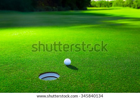 Golf ball on a green lawn - stock photo