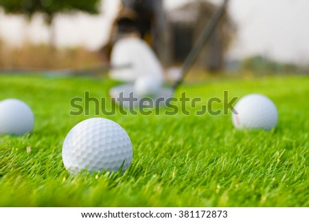 Golf ball on a sloping green at sunset