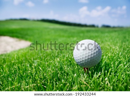 Golf ball on a tee against golf course - stock photo