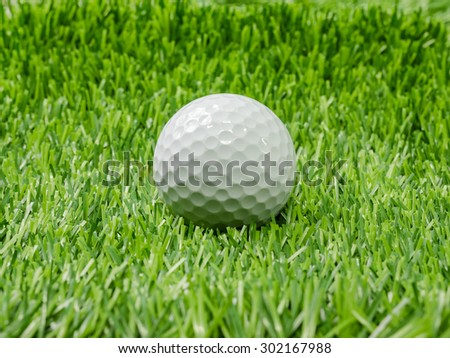 Golf ball on course with green grass. - stock photo