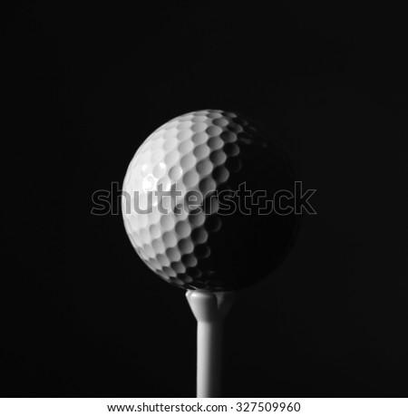 Golf ball on dark background - stock photo