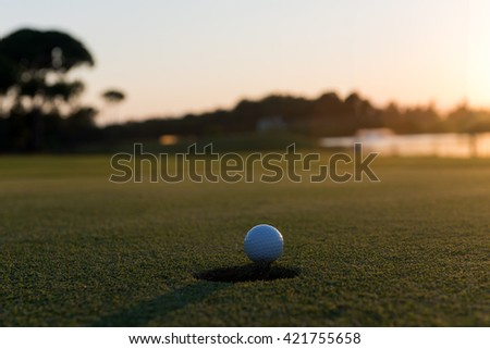 golf ball on edge of course hole representing achivement and success business concept, beautiful sunset in background - stock photo