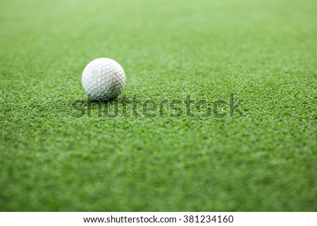 Golf ball on green field during sunset