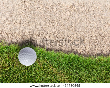 Golf ball on green grass near sand bunker - stock photo