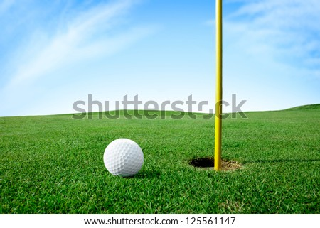 Golf ball on green grass next hole