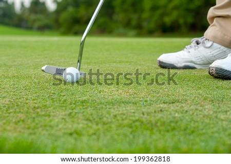 Golf ball on green meadow - stock photo