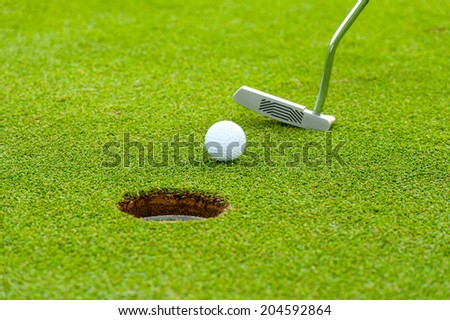 Golf ball on green meadow - stock photo