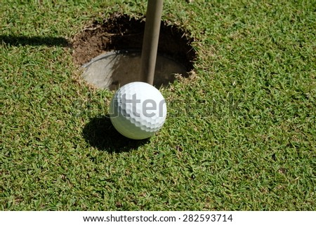 Golf ball on green meadow. golf ball on lip of cup