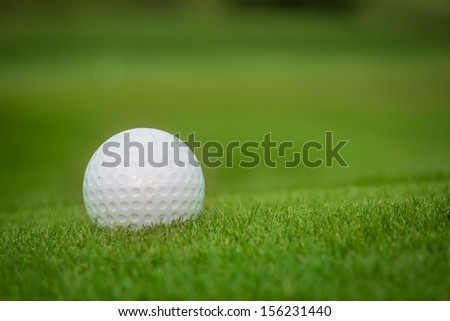 Golf ball on green over a blurred green. Shallow depth of field. Focus on the ball - stock photo