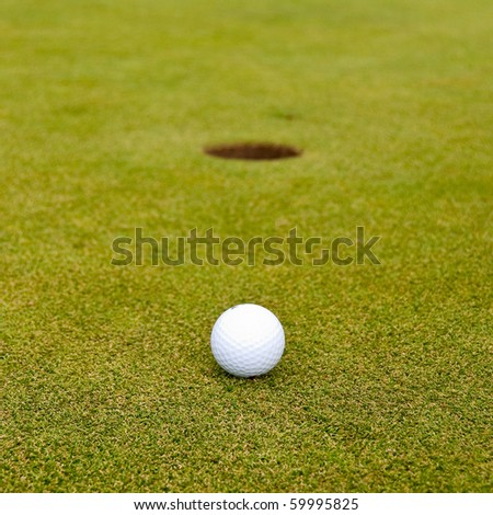Golf ball on green over a blurred hole. Shallow depth of field. Focus on the ball. - stock photo