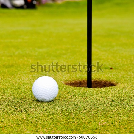 Golf ball on green with flag. Shallow depth of field. Focus on the ball. - stock photo