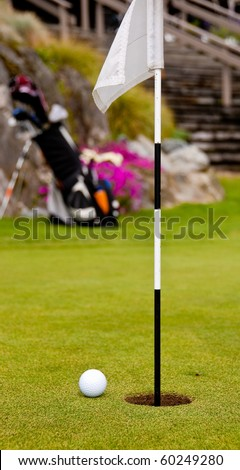 Golf ball on green with flag. Shallow depth of field. Focus on the ball and the hole. - stock photo