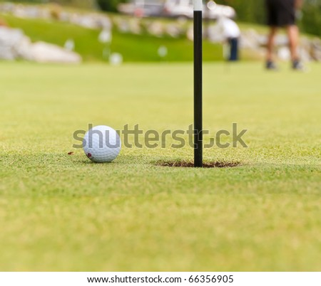 Golf ball on green with flag. Shallow depth of field. Focus on the ball and the hole.